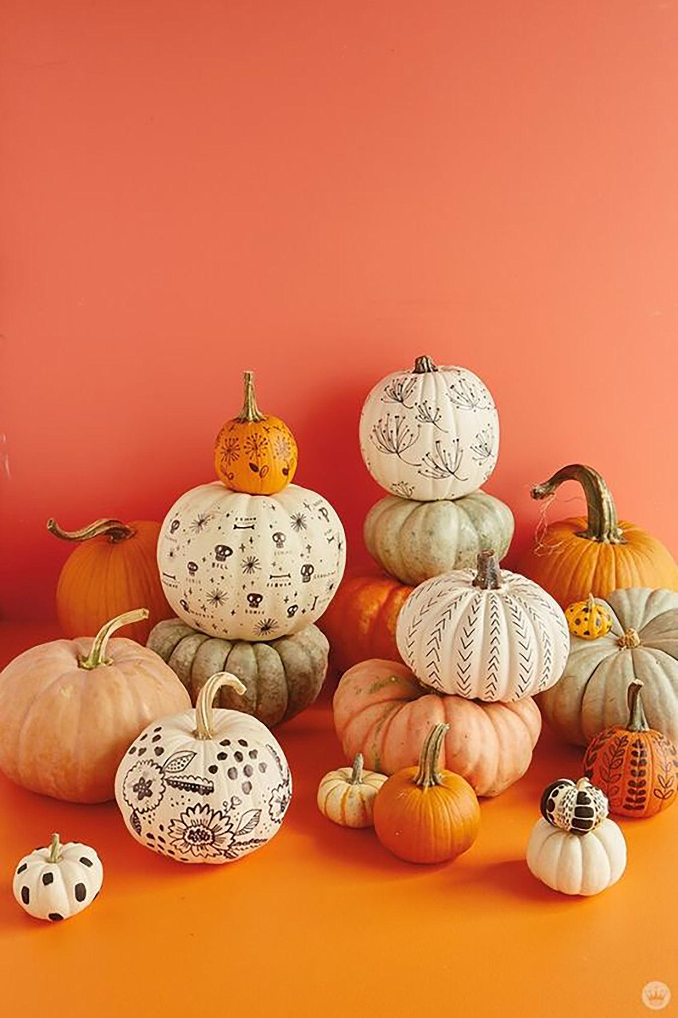 An arrangement of different sized painted pumpkins in front of an orange wall