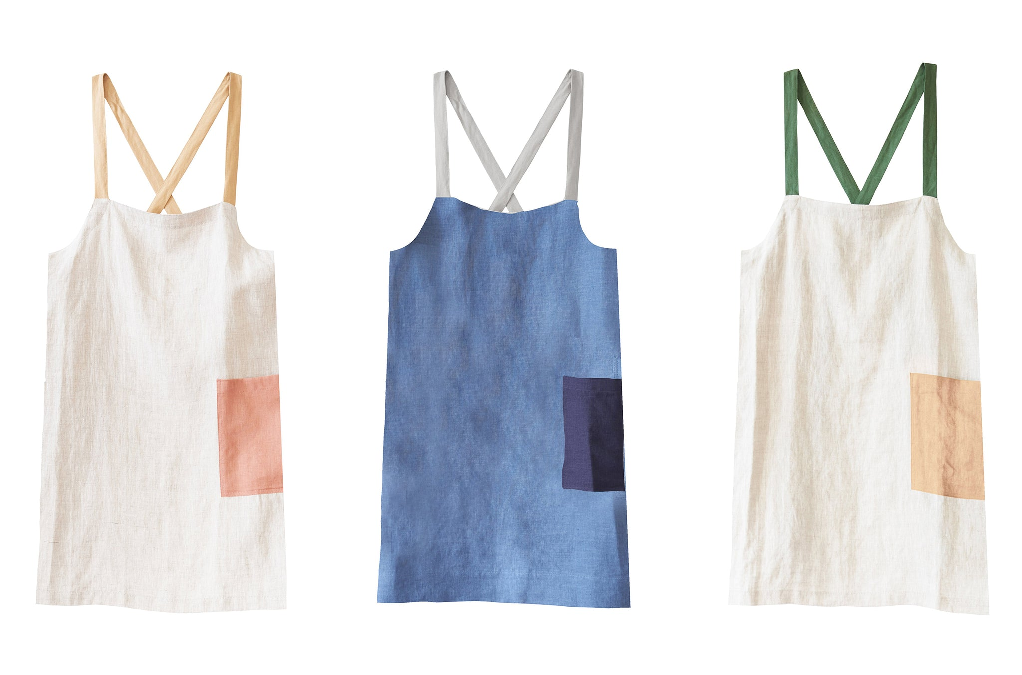 three aprons in sand color with pink pocket, indigo color with dark blue pocket, sand color with tan pocket and green straps