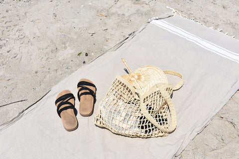 bag and shoes on beach towel