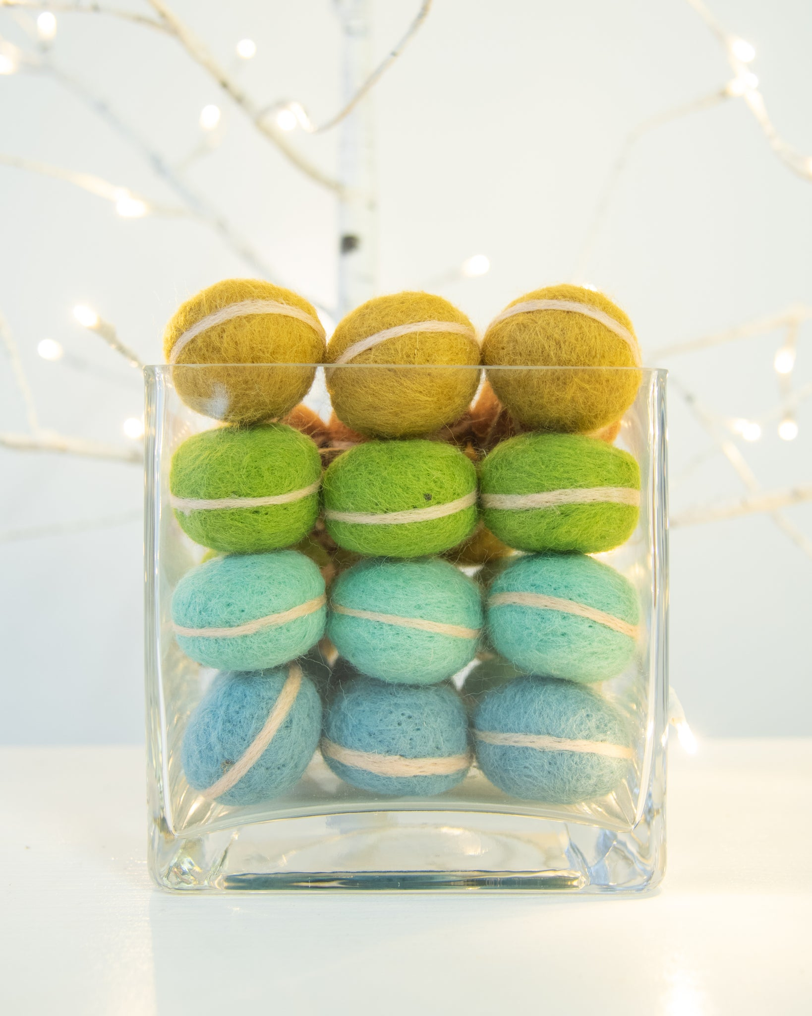 bowl full of colorful french macaron ornaments in front of white christmas lights