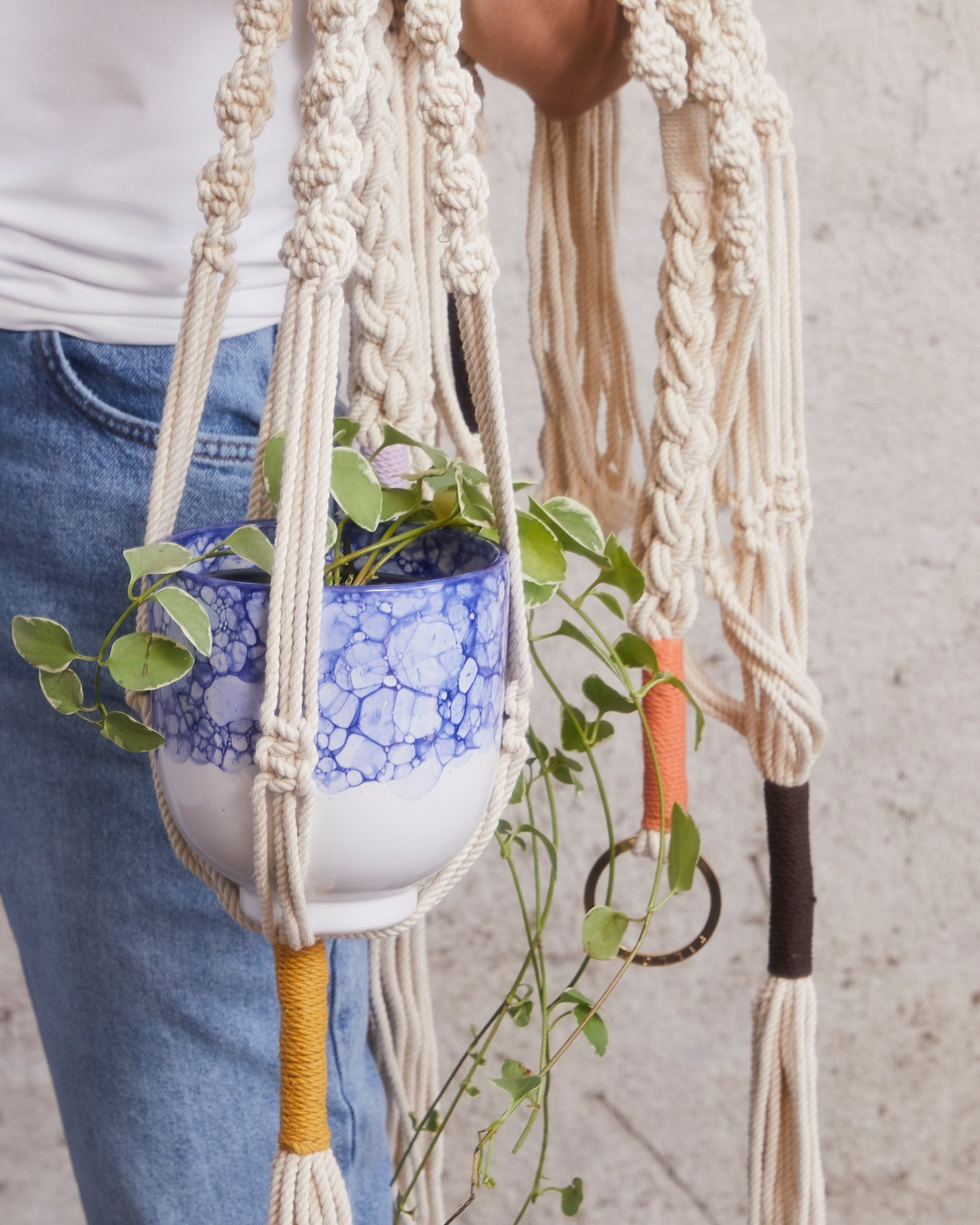 close up of woman holding multiple macrame plant hangers with different color knots