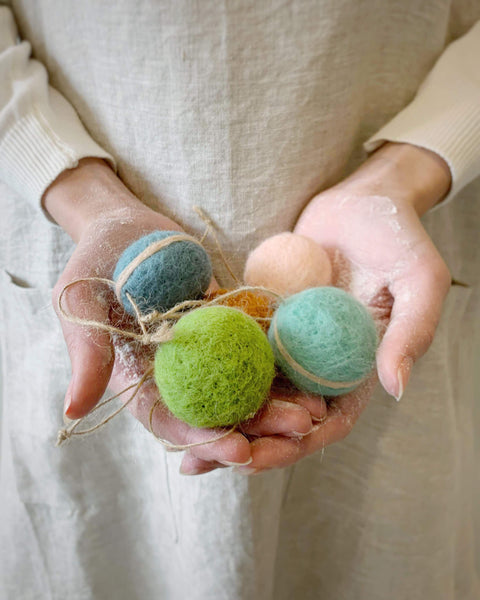 two hands holding colored felt macarons