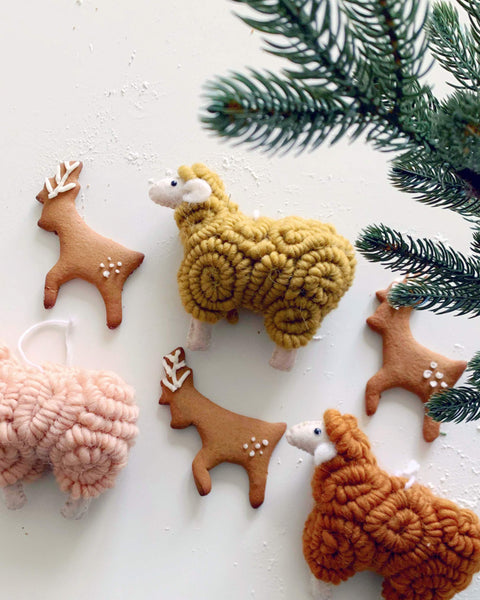 reindeer shaped gingerbread cookies, sheep ornaments, on white table