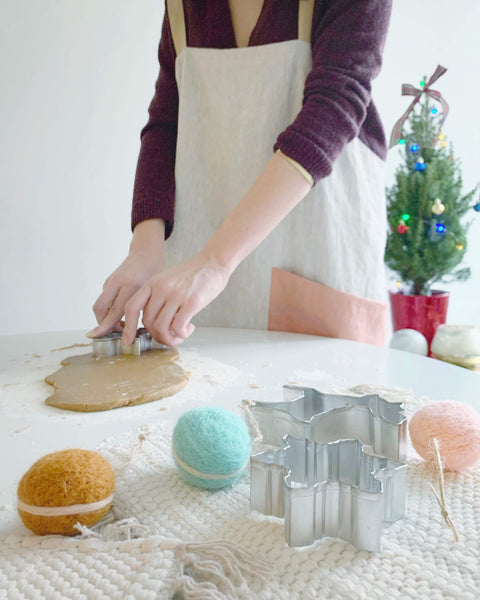 woman wearing apron, cookie cutters and dough on table
