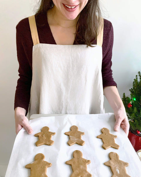 woman holding tray of gingerbread men