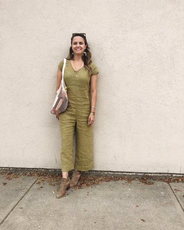 woman leaning against a wall wearing a green jumpsuit