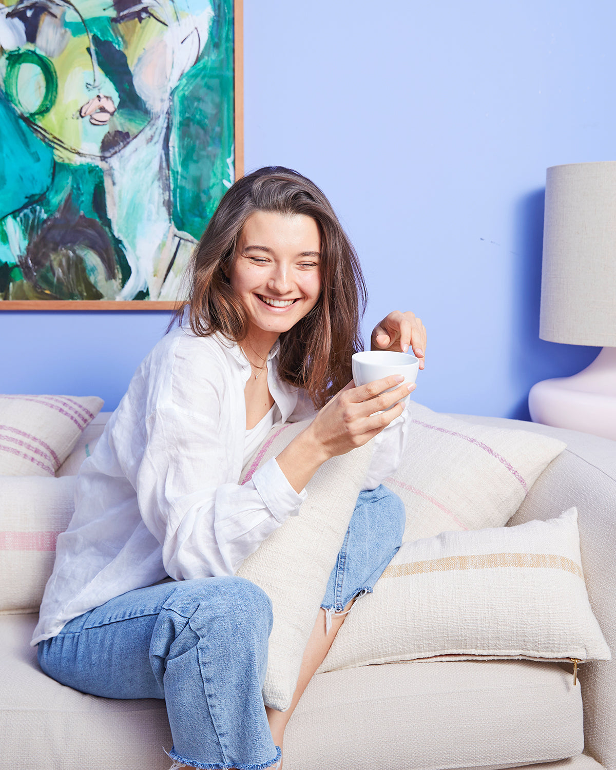 Woman laughing holding cup of coffee on a couch filled with pillows