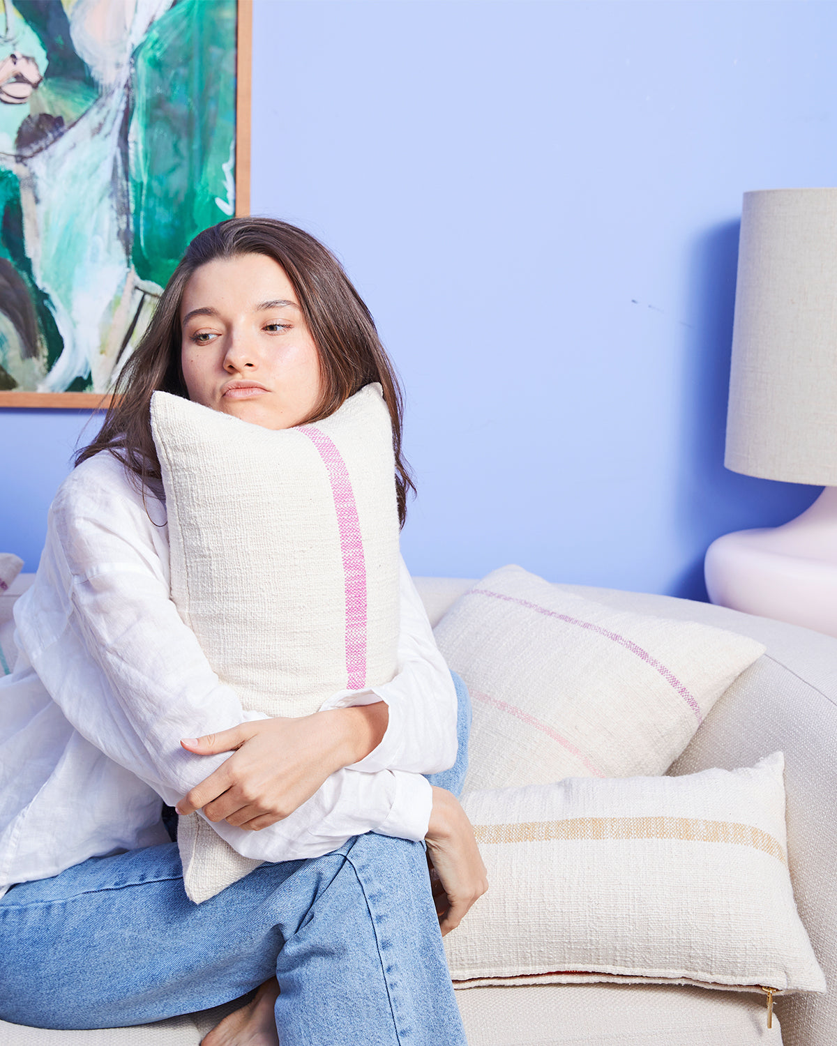 Woman sitting holding a striped pillow on a couch filled with pillows