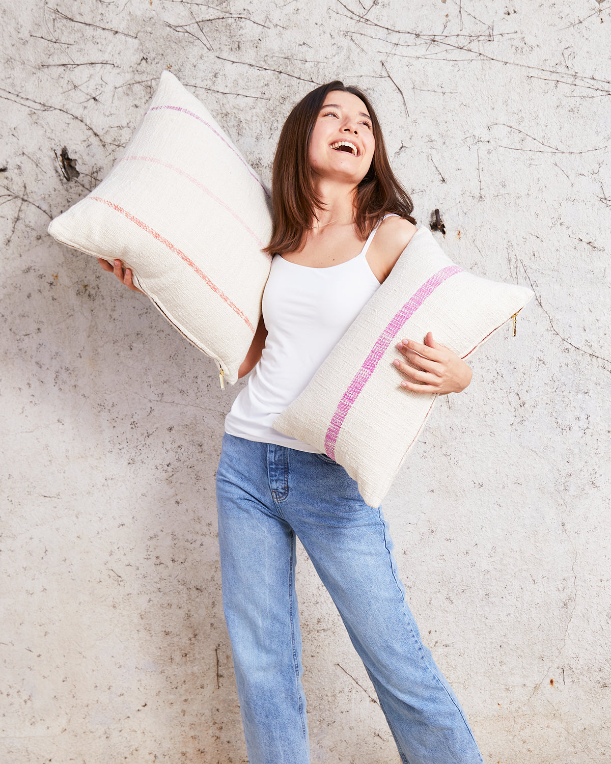 woman holding two striped pillows