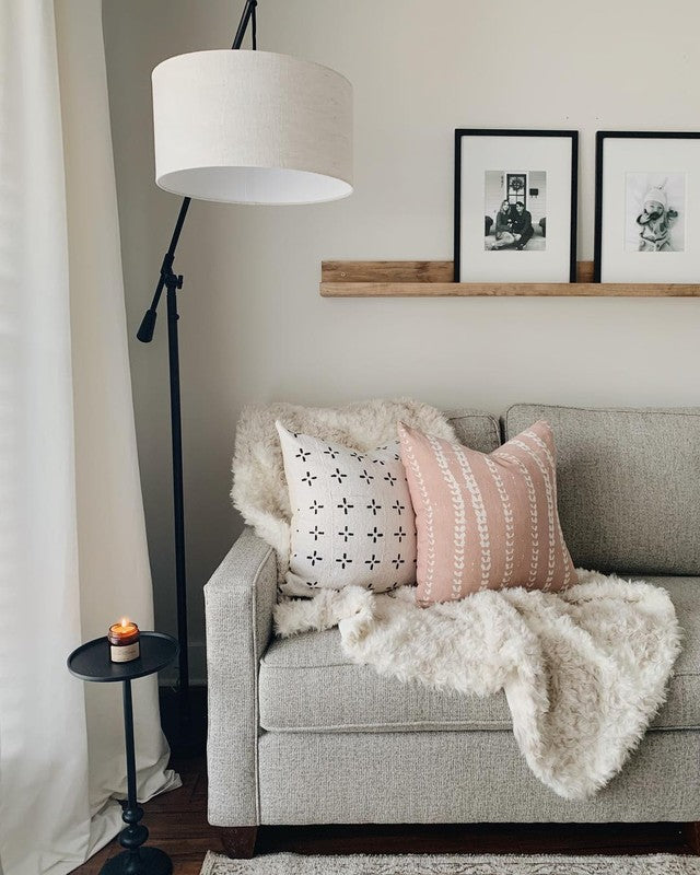 cloreup of couch with two printed pillows and a throw blanket
