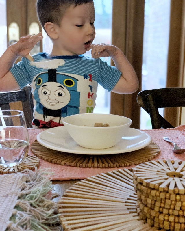 little boy sitting at table, table covered with coasters and placemats