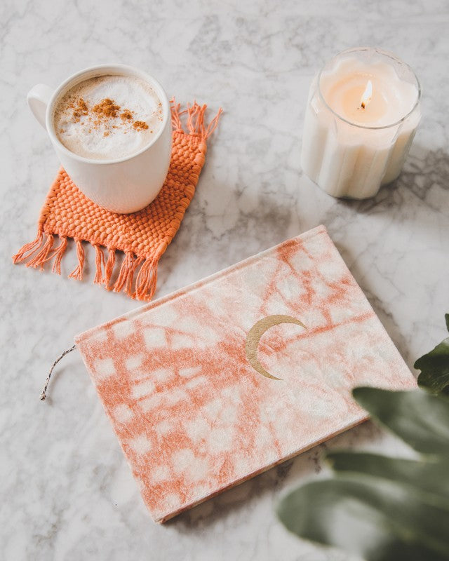 coffee mug on top of orange rug coaster, orange journal, white lit candle