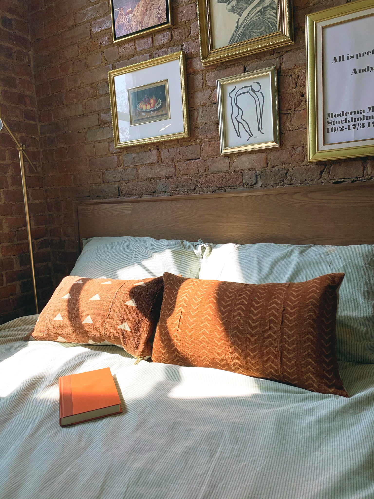A closeup of a bed in front of a brick wall with gold picture frames. two long rust colored mud cloth pillows and an orange book on top of bed.