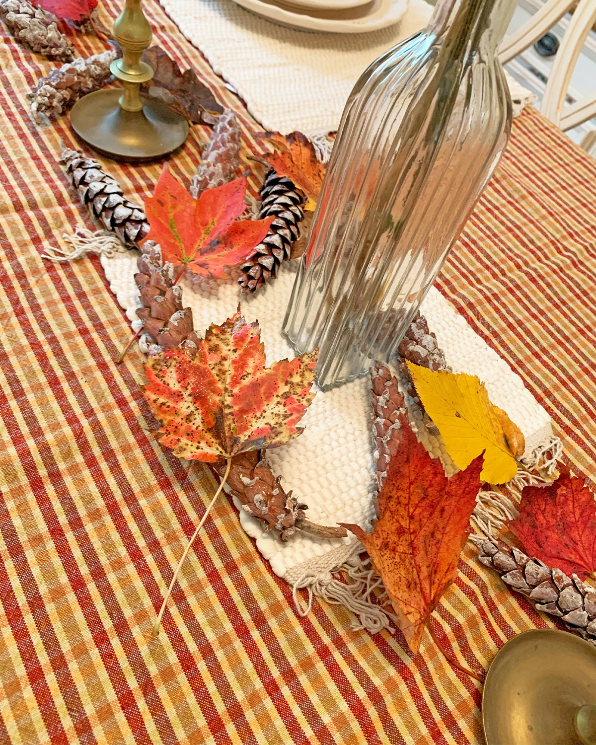 Closeup of table scape with orange and red checkered tablecloth, small white rug hot pad under neath a cluster of red and orange leaves and pinecones, a glass bottle in center filled with dried flowers.