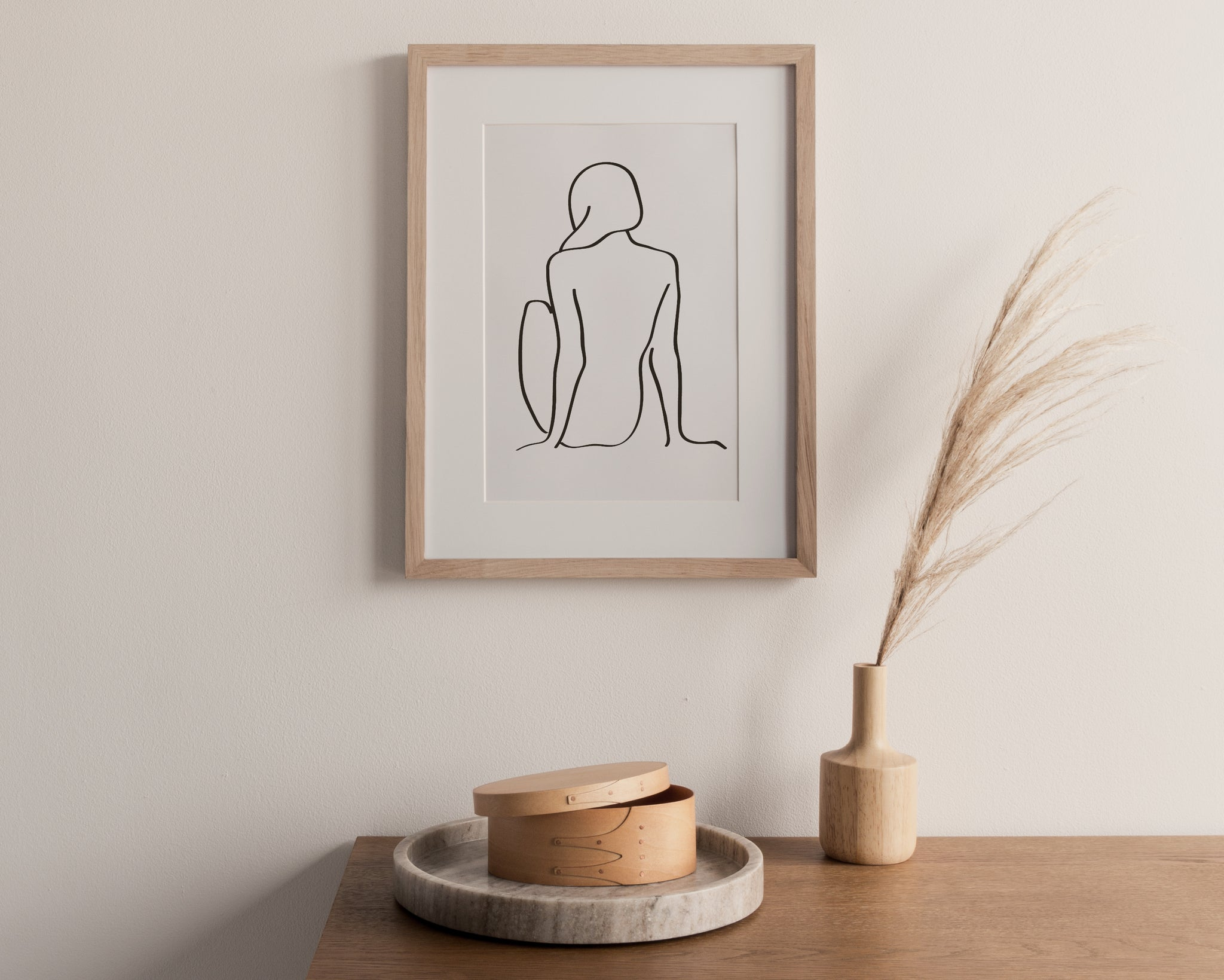 framed print of a drawing of a girl sitting. frame on a cream wall with table below