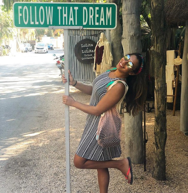 woman posing with street sign wearing dress