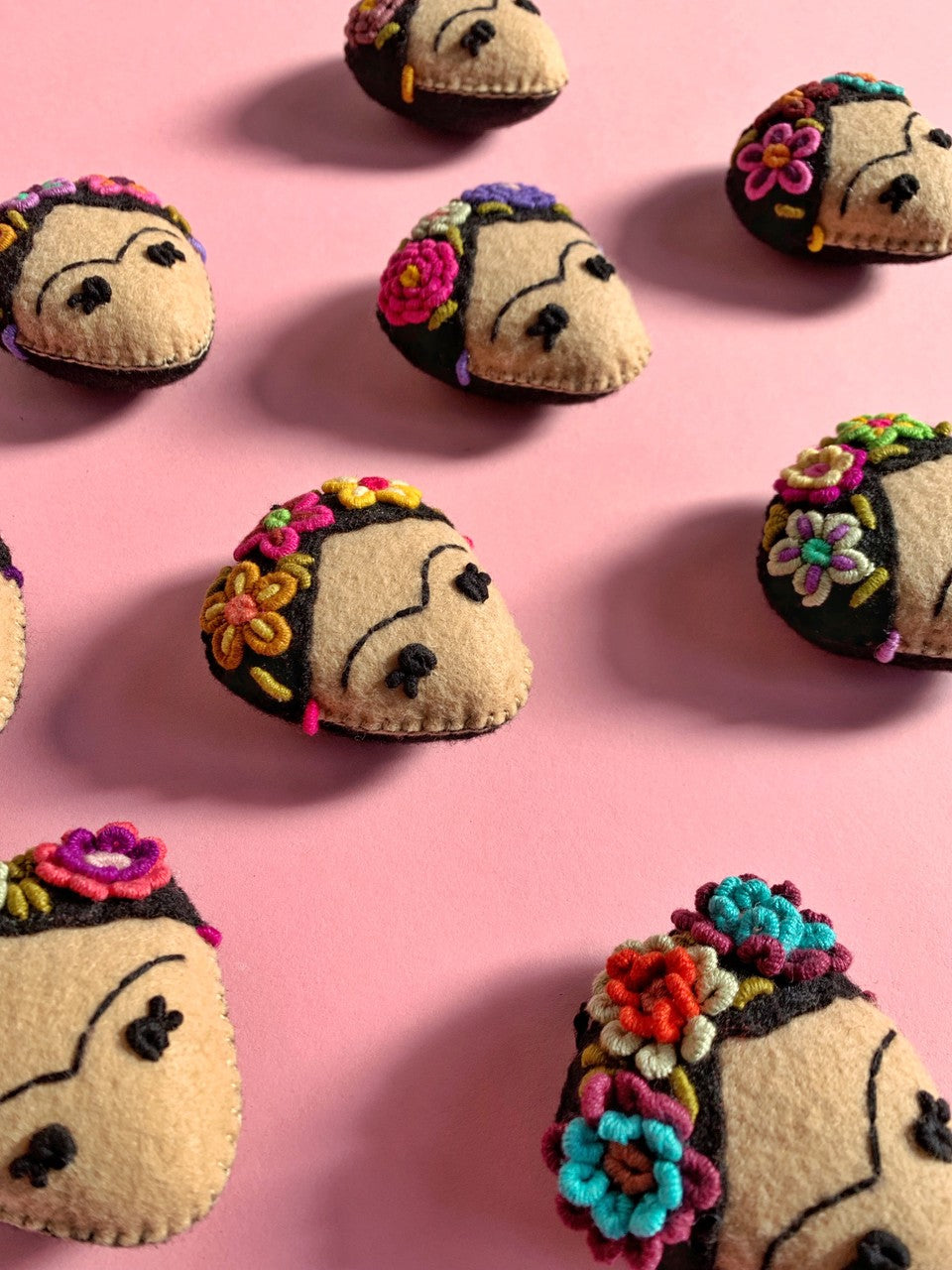 hand sewn Frida Kahlo head ornaments laid out on a pink table