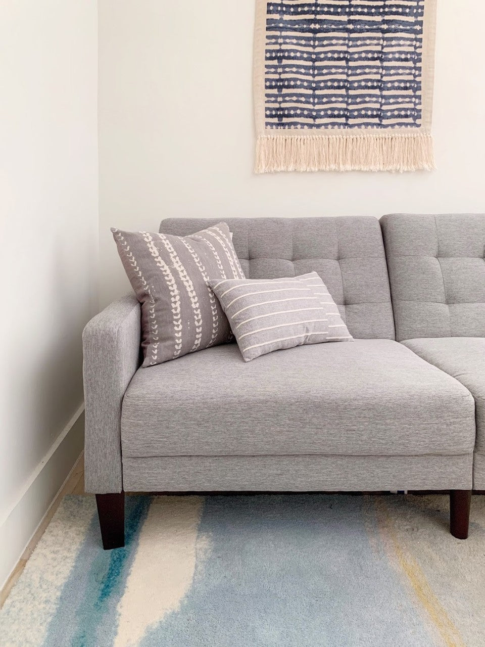 grey couch with two printed grey pillows on top, in front of white wall. Pastel water colored rug on floor
