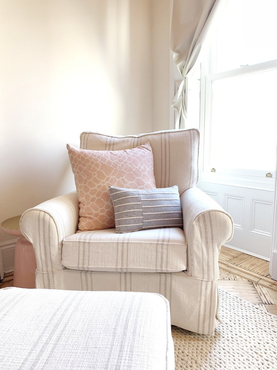 white and grey striped arm chair with large pink pillow and grey lumbar pillow on top in front of white wall