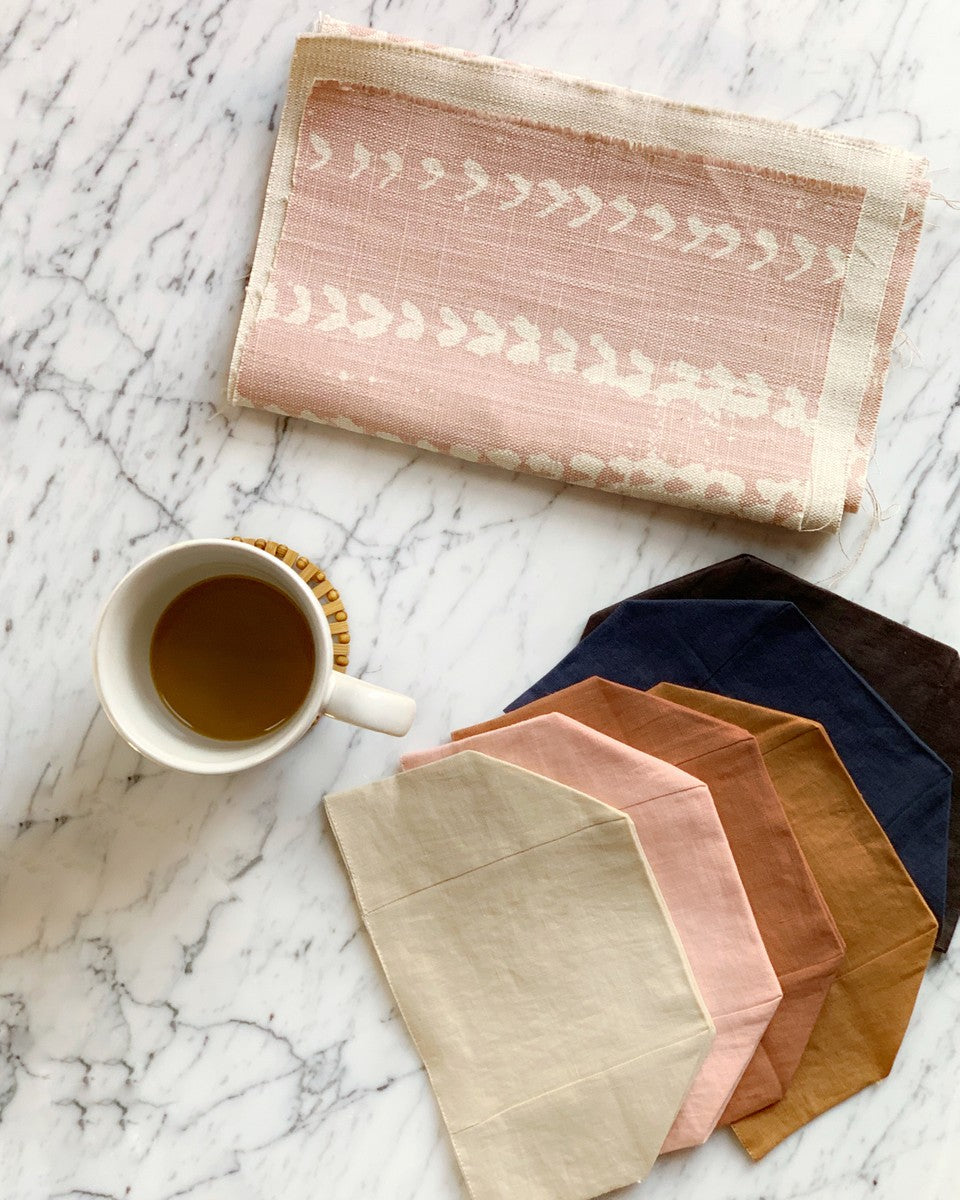 marble table with cup of coffee, six linen tissue box colors splayed in various earthy colors, folded pink fabric