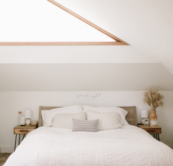 white bedroom with wooden side tables and bedframe. white linens with grey lumbar pillow on top of bed