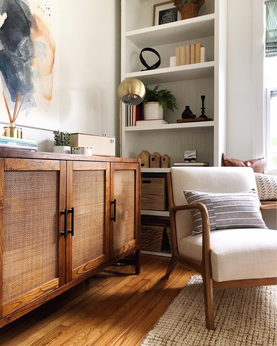 living room corner with wooden cabinet and white chair with grey striped lumbar pillow on top
