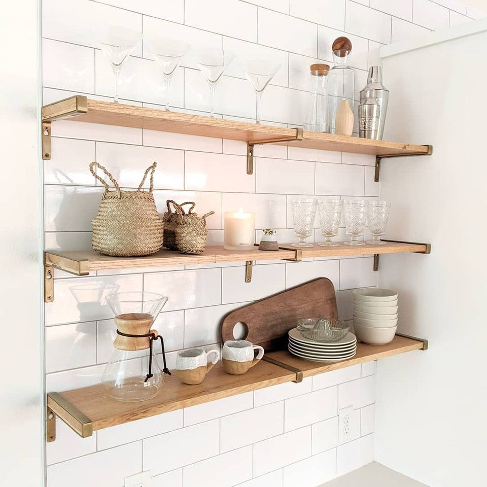 kitchen wall shelves with various glasses and wooden cutting boards. Three bamboo belly baskets together on middle shelf.