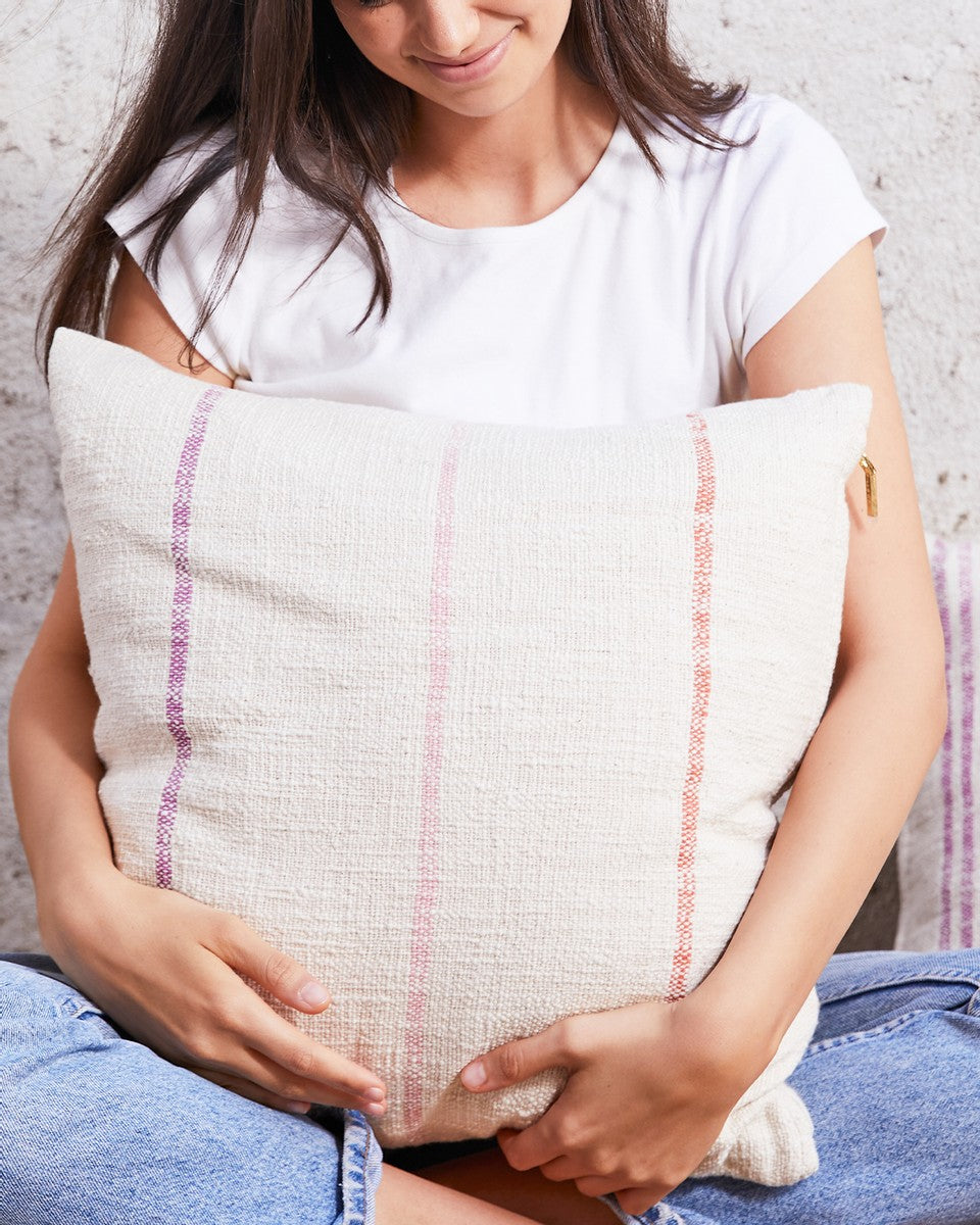 woman sitting with a striped pillow in her lap