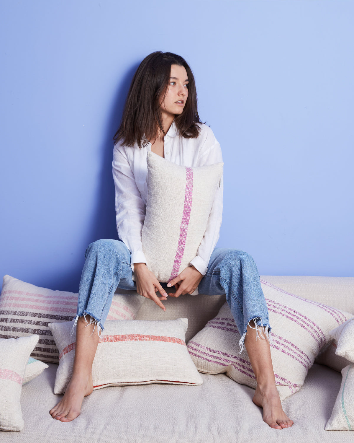 woman sitting on couch with a bunch of pillows. holding a lumbar pillow with a purple stripe