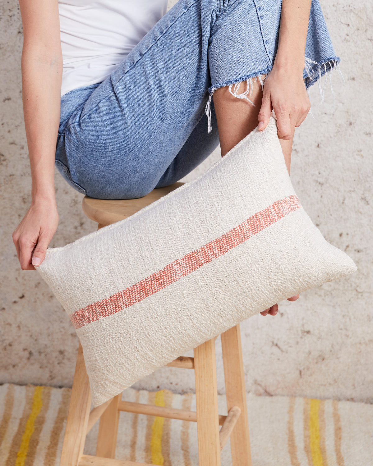 lumbar pillow with orange stripe in front of a stool