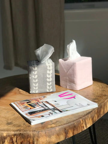 two tissue boxes with covers and magazine on coffee table