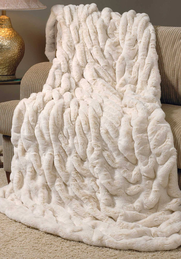 Ivory faux fur throw blanket on chaise