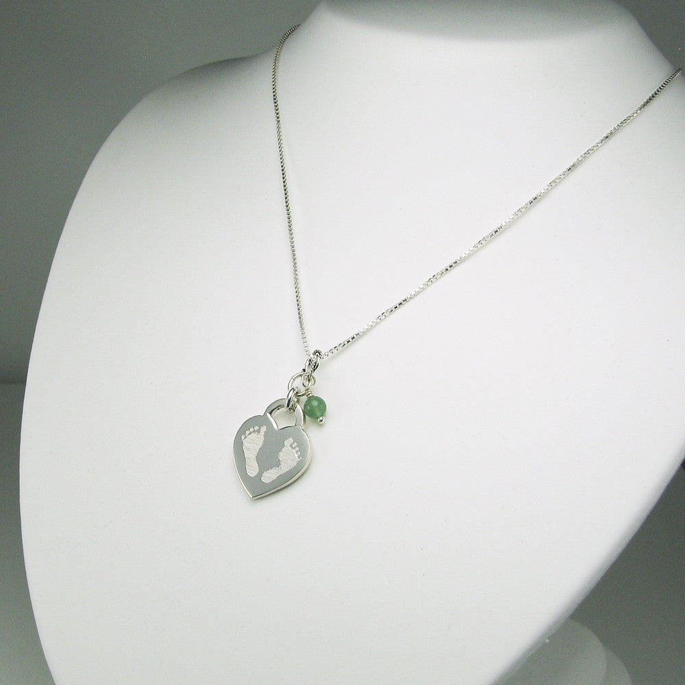 Our signature baby footprints image engraved on front of medium sterling silver heart charm. Shown with May-Aventurine gem bead dangle and sterling silver box chain
