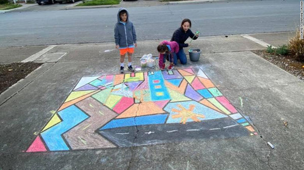 Daphne Sashin, her 8-year-old son Jack and 5-year-old daughter Lucy work on their sidewalk drawing as part of the community activity Sashin planned in their Mountain View, California, neighborhood. (via CNN)