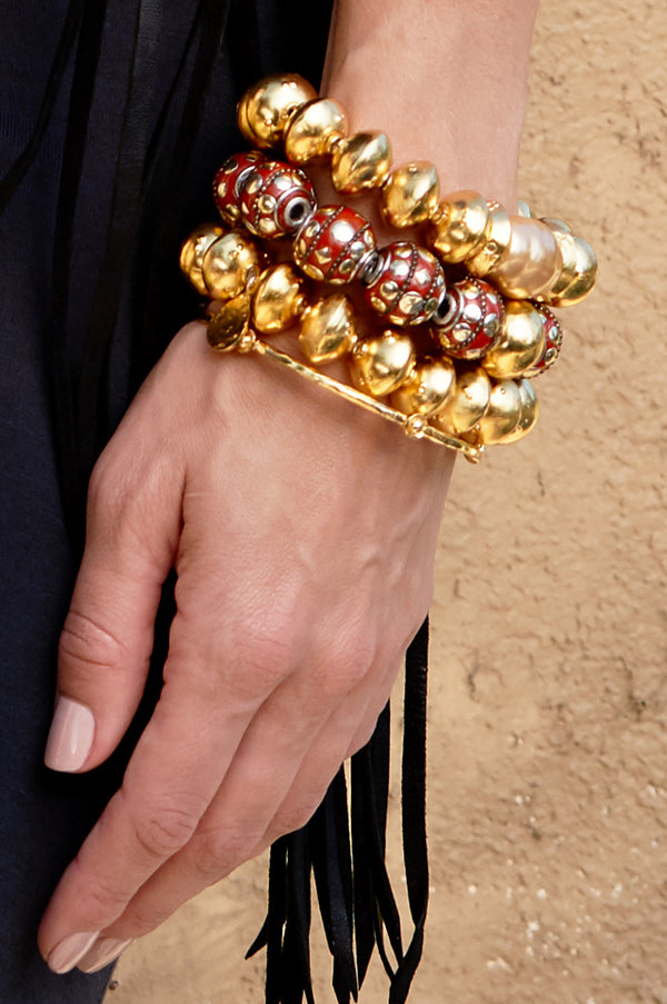 High end statement bracelet with large red beads and 18K gold detail.