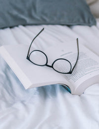 Strategy and marketing blog - Glasses on top of book in bed.
