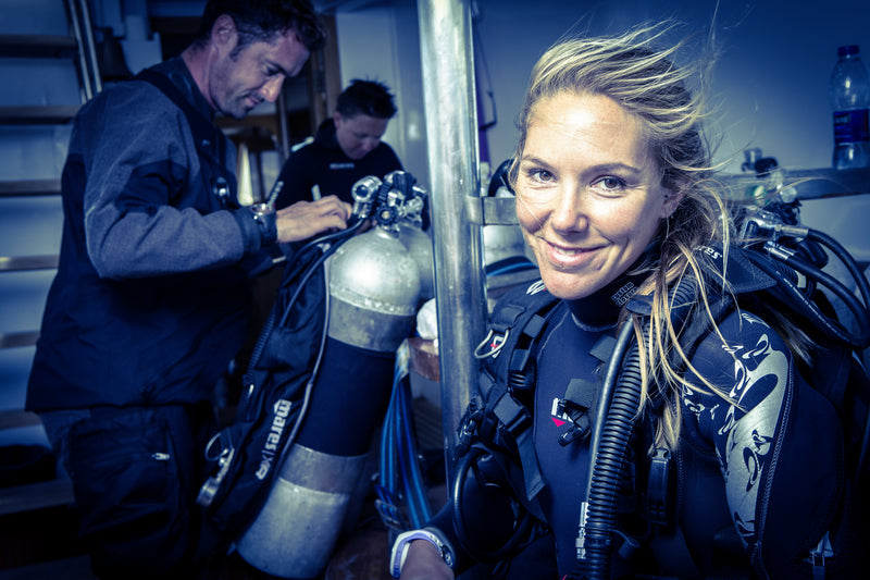 Divers preparing their equipment while wearing exposure suits
