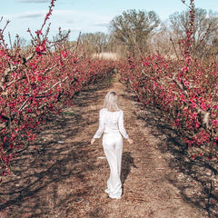 Full in bloom - stunning traveler @alittleblondinparadise striding in our Pleated Silk Palazzo Pants in Aitona