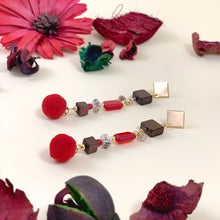 Load image into Gallery viewer, Long dangle earrings with red pom poms, glass and wooden beads - lying on a surface among dry flowers