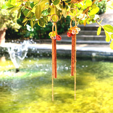 Load image into Gallery viewer, Cute wood long dangle earrings with colorful glass beads and gold-plated chain hanging on a plant in a garden