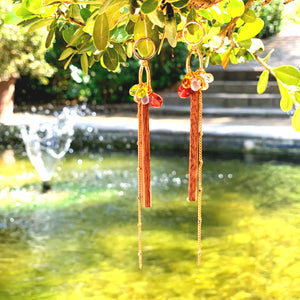 Cute wood long dangle earrings with colorful glass beads and gold-plated chain hanging on a plant in a garden