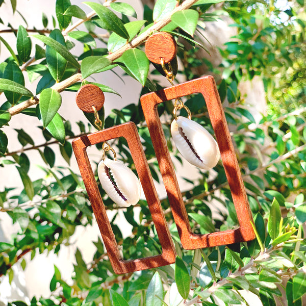 Branch of a tree with rectangular natural Sapele hard wood earrings with dangling Cowrie shells