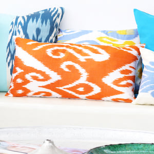 Ikat decorative pillows in orange, blue and turquoise on a sofa