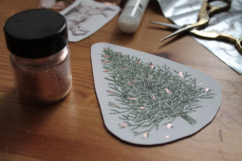 Making Christmas decorations. Christmas tree decoration with copper embossing lies on table with glitter, scissors and glue.