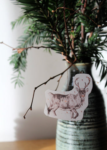 Reindeer decoration hanging in Christmas branches