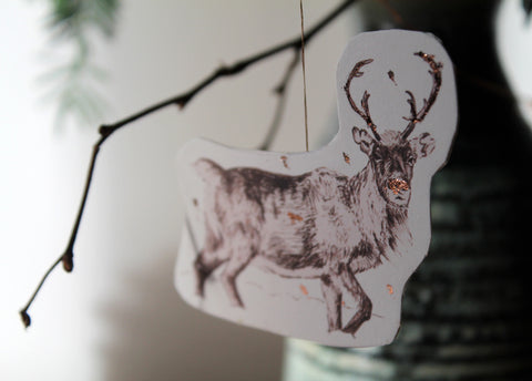 Reindeer decoration with copper embossing hanging in Christmas branches