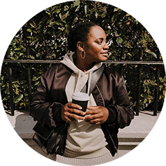 Sasha, a black woman looking to her left hand side holding a coffee and leaning against some railings
