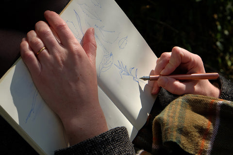 Agnes Becker sketches outside - close up of hand sand sketchbook