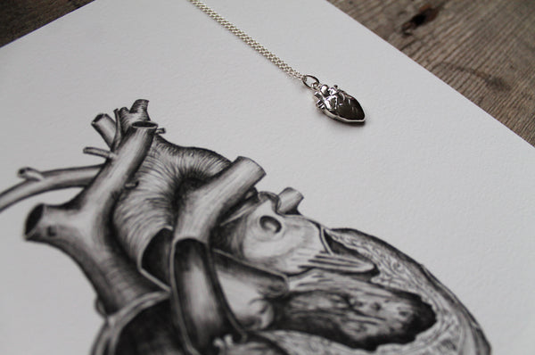 close up of anatomical heart print on rustic wooden table with sterling silver anatomical heart pendant lying on top right of print