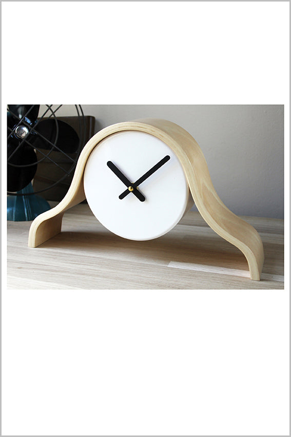 Wood frame, white mantel clock, black hands, on shelf